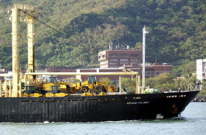 KAOHSIUNG, TAIWAN -- AUGUST 12, 2015: The Panamanian freighter Grand Tajima enters Kaohsiung Port with a cargo of construction equipment and excavators.